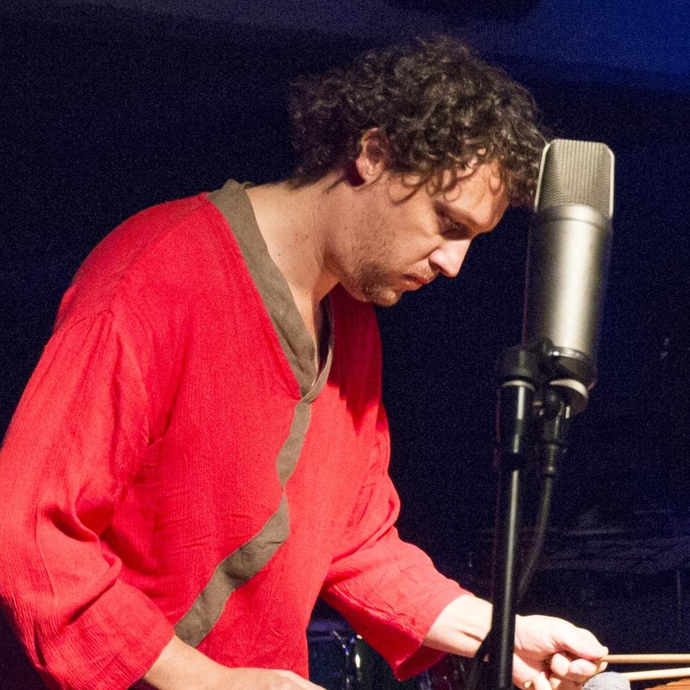 Hombre de camisa roja tocando instrumento de percusion