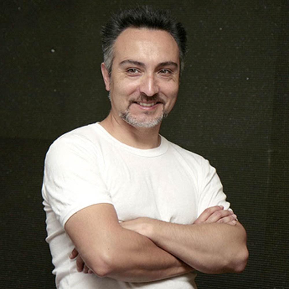 Hombre de polera blanca con brazos cruzados