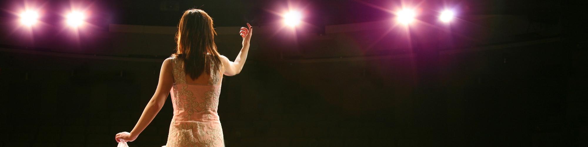 mujer sobre el escenario con luces arriba