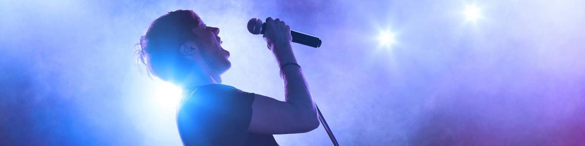 mujer cantando sobre escenario azul