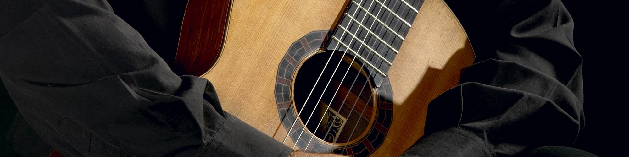 musico sosteniendo guitarra clasica