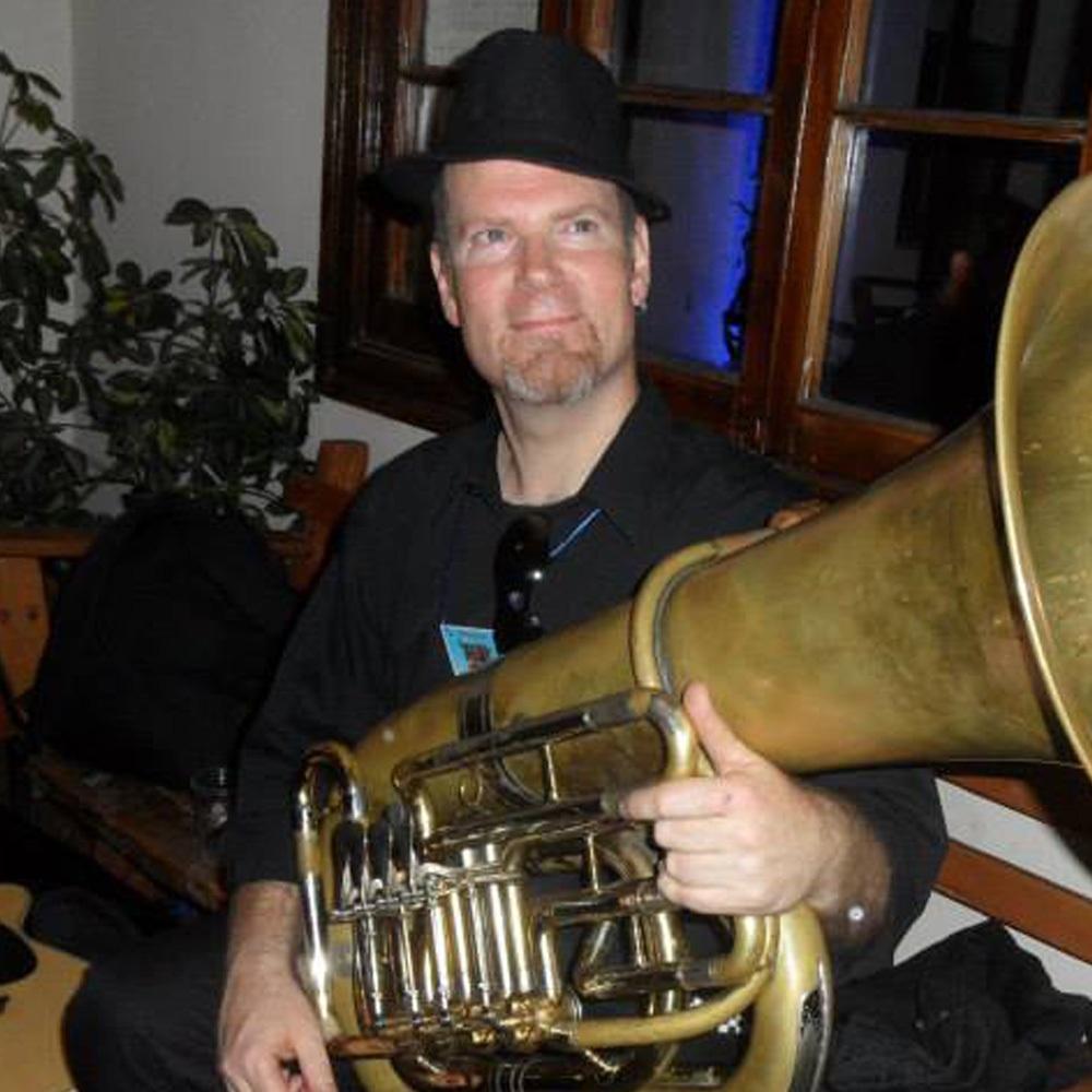 hombre con sombrero cargando una tuba