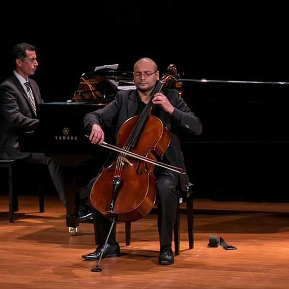 Hombre vestido de negro tocando el violoncello con pianista de fondo