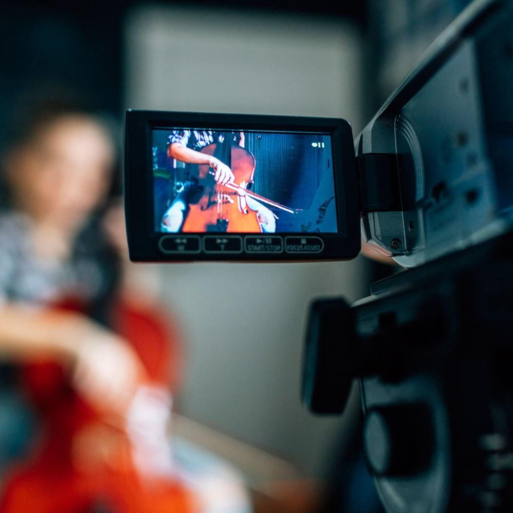 mujer tocando contrabajo mientras es filmada
